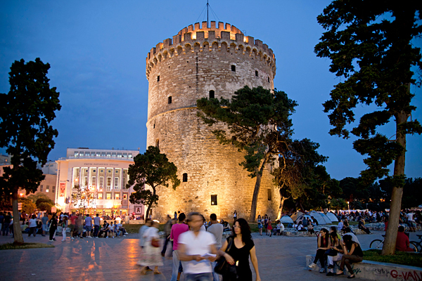 a busy evening at the illuminated white tower, symbol of the town of Thessaloniki, Macedonia, Greece